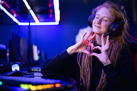 Streamer beautiful girl shows heart sign with hands professional gamer playing online games computer, neon color